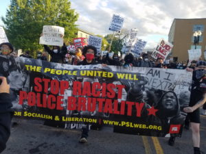 "Party for Socialism and Liberation PSL members march in Boston. The banner they hold reads ""The people united will stop racist police brutality."""